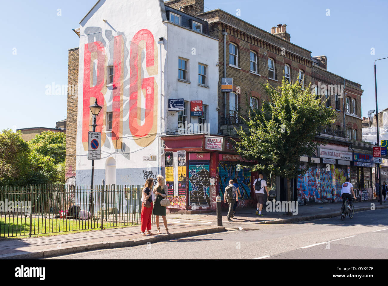 People walking on Hackney road in Bethnal Green, East London, on a sunny day. - Stock Image