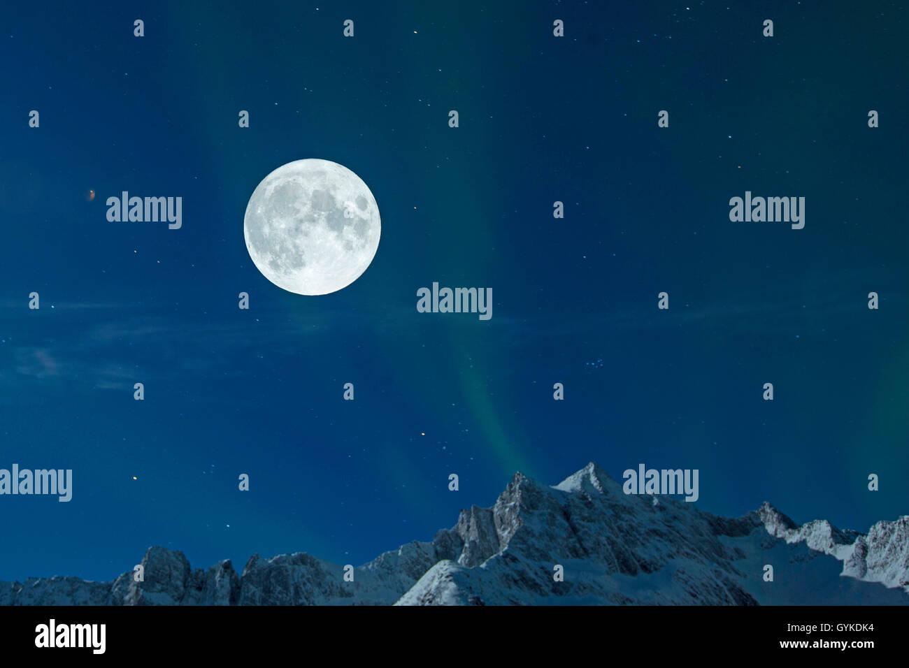 Vollmond mit Sternenhimmel und Nordlicht ueber Berggipfeln, Norwegen, Troms, Senja   full moon with starry sky and - Stock Image