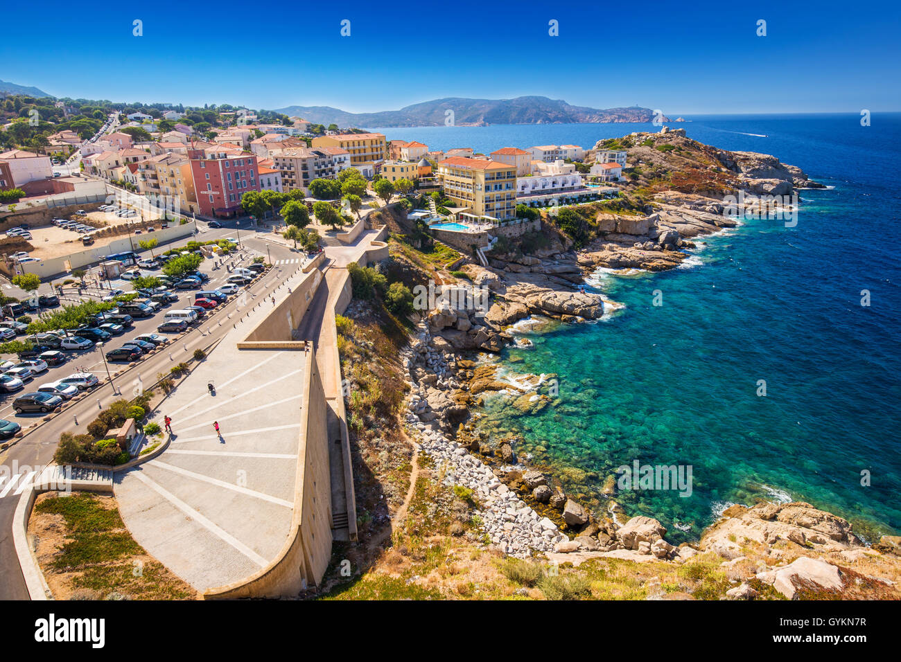 View to beautiful Corsica coastline and historic houses in Calvi old town with turquoise clear ocean water, Corsica, - Stock Image