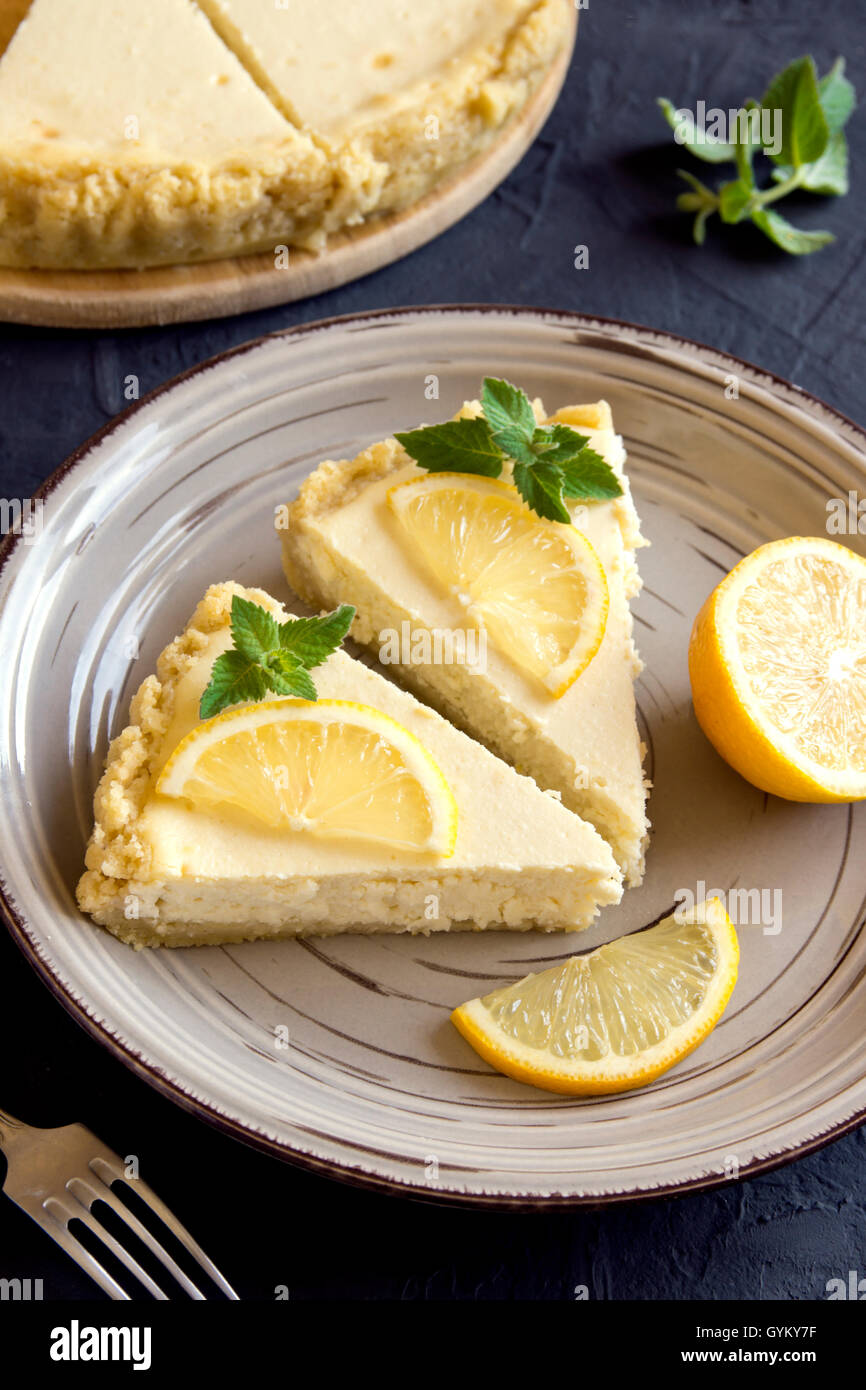 Pieces of delicious homemade lemon cheesecake with slices of lemon and mint on plate close up - Stock Image