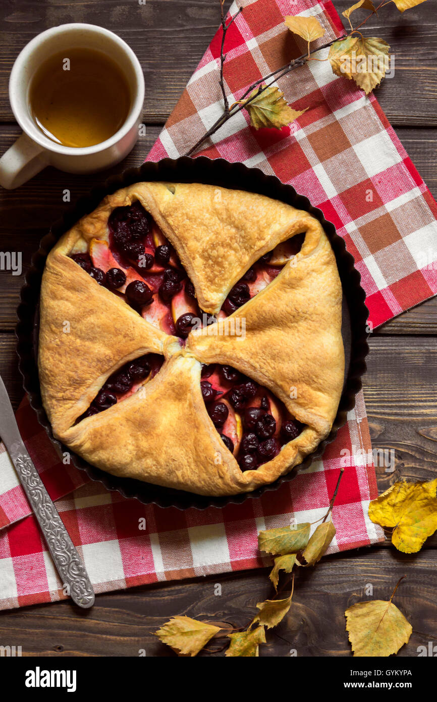 Homemade cherry and apple pie over rustic wooden background with yellow leaves - delicious autumn pastry - Stock Image