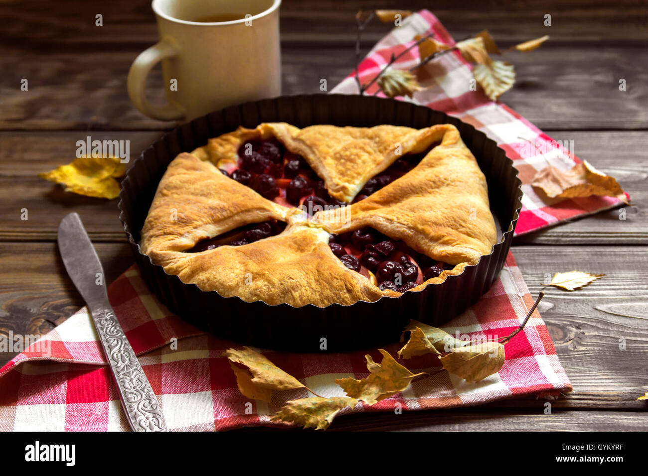 Homemade cherry and apple pie over rustic wooden background with yellow leaves, copy space - delicious autumn pastry - Stock Image