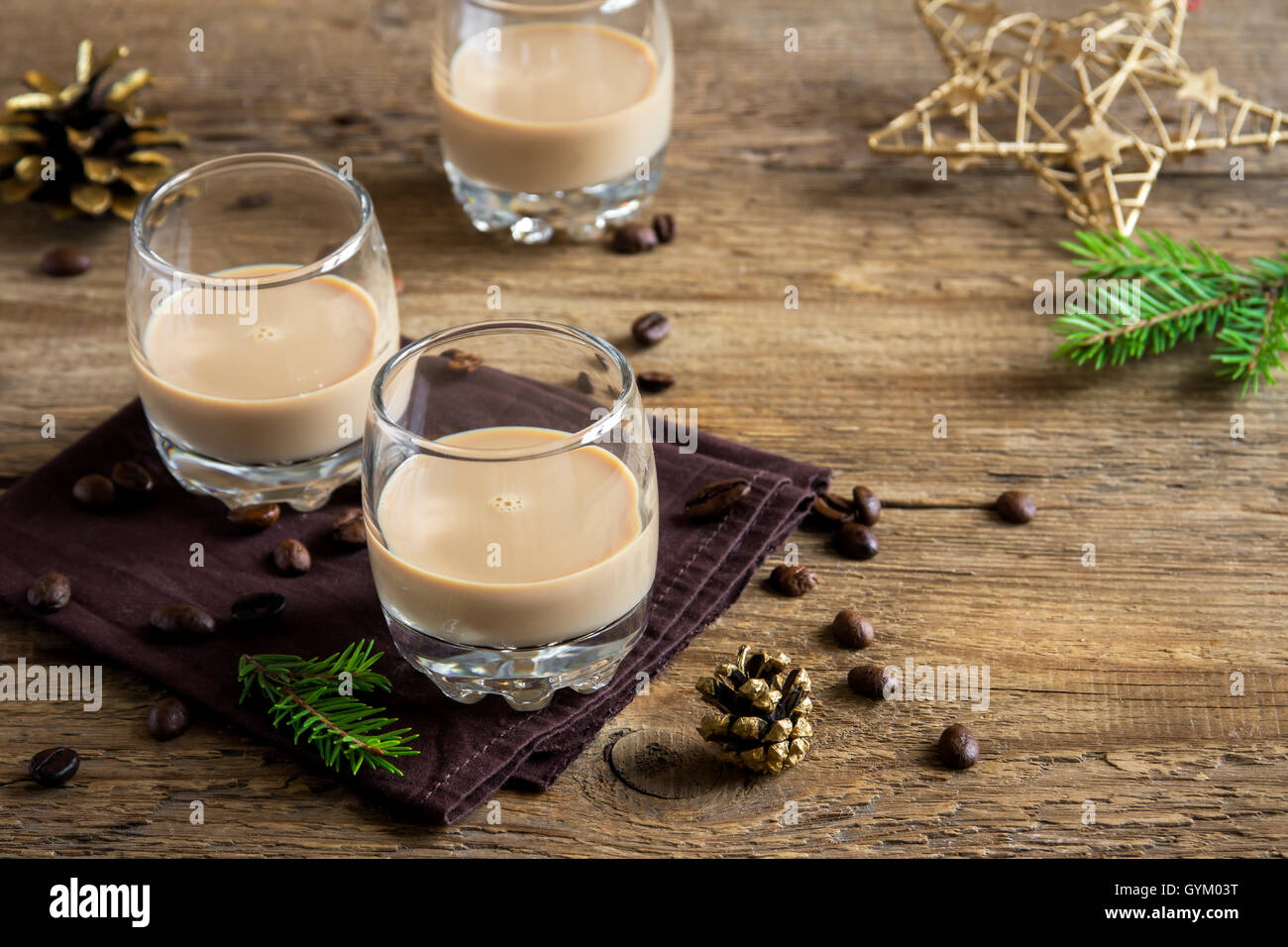 Irish cream coffee liqueur with Christmas decoration and ornaments over rustic wooden background - festive Christmas alcoholic d Stock Photo