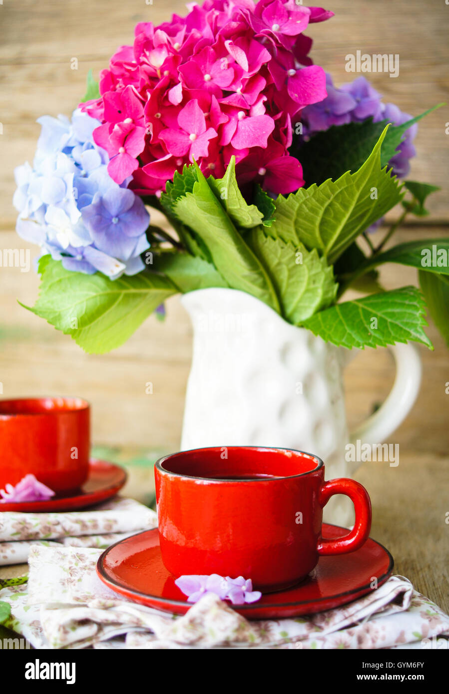 hydrangea flowers in a vase and cup of coffee on the wooden table