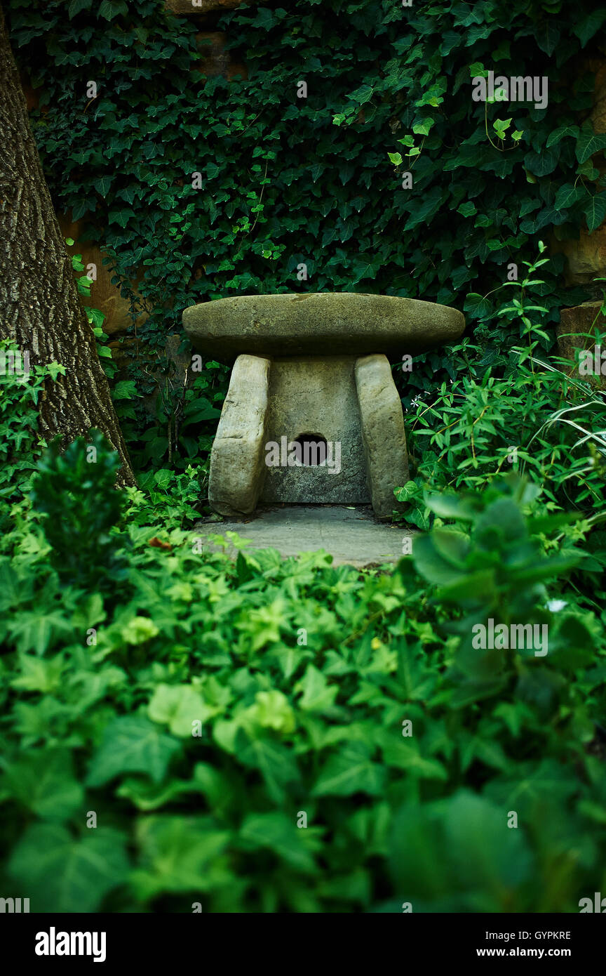 small figure of a dolmen in the green thickets. Symbol - Stock Image