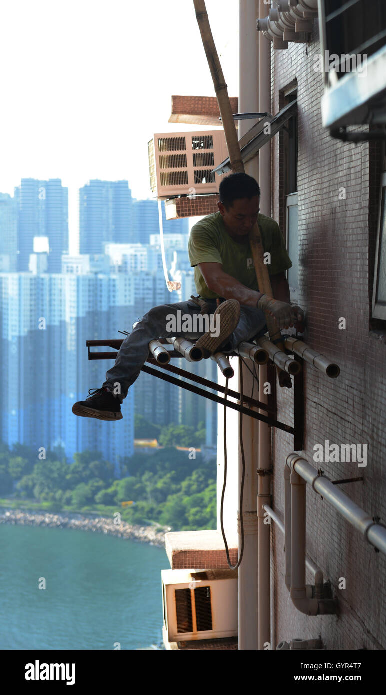 A construction worker on a very high scaffolding in Hong Kong. Stock Photo