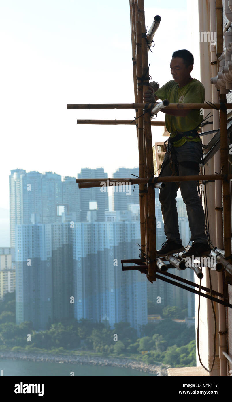 A construction worker on a very high scaffolding in Hong Kong. - Stock Image