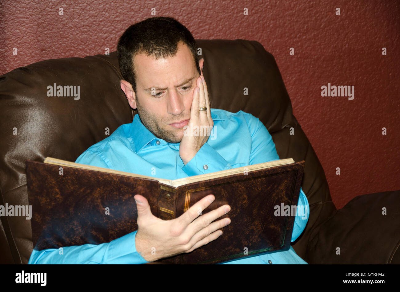 Man reminiscing looking at an old photo album. - Stock Image