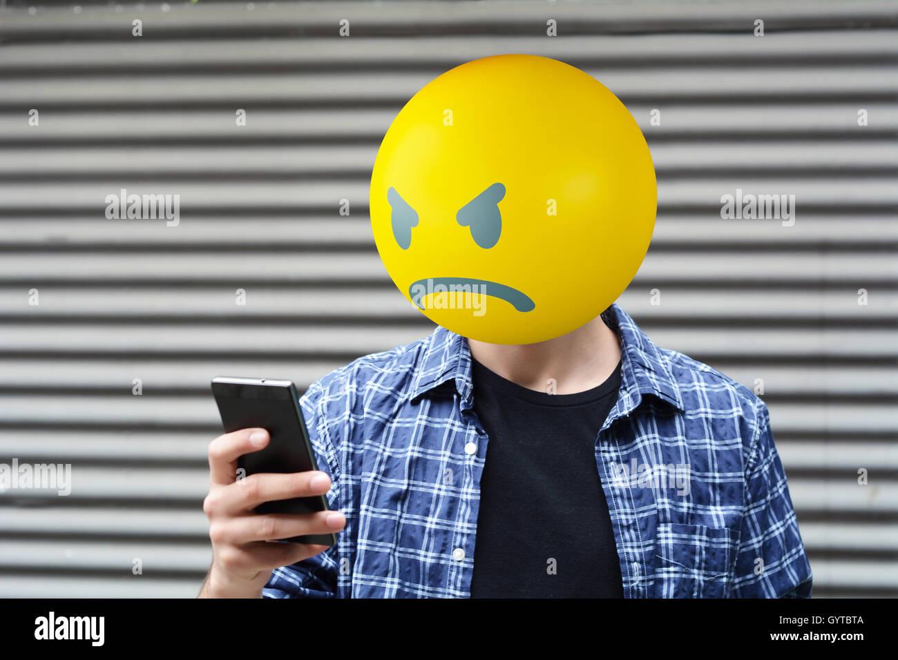 Angry emoji head man using a smartphone. - Stock Image