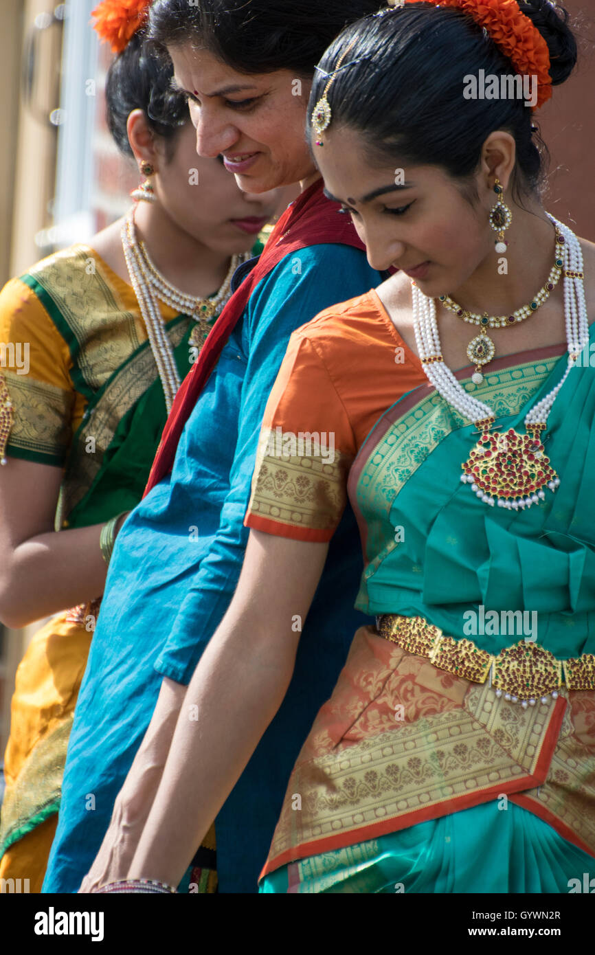 Indian mother and daughter dressed on sidewalk at street fair. - Stock Image