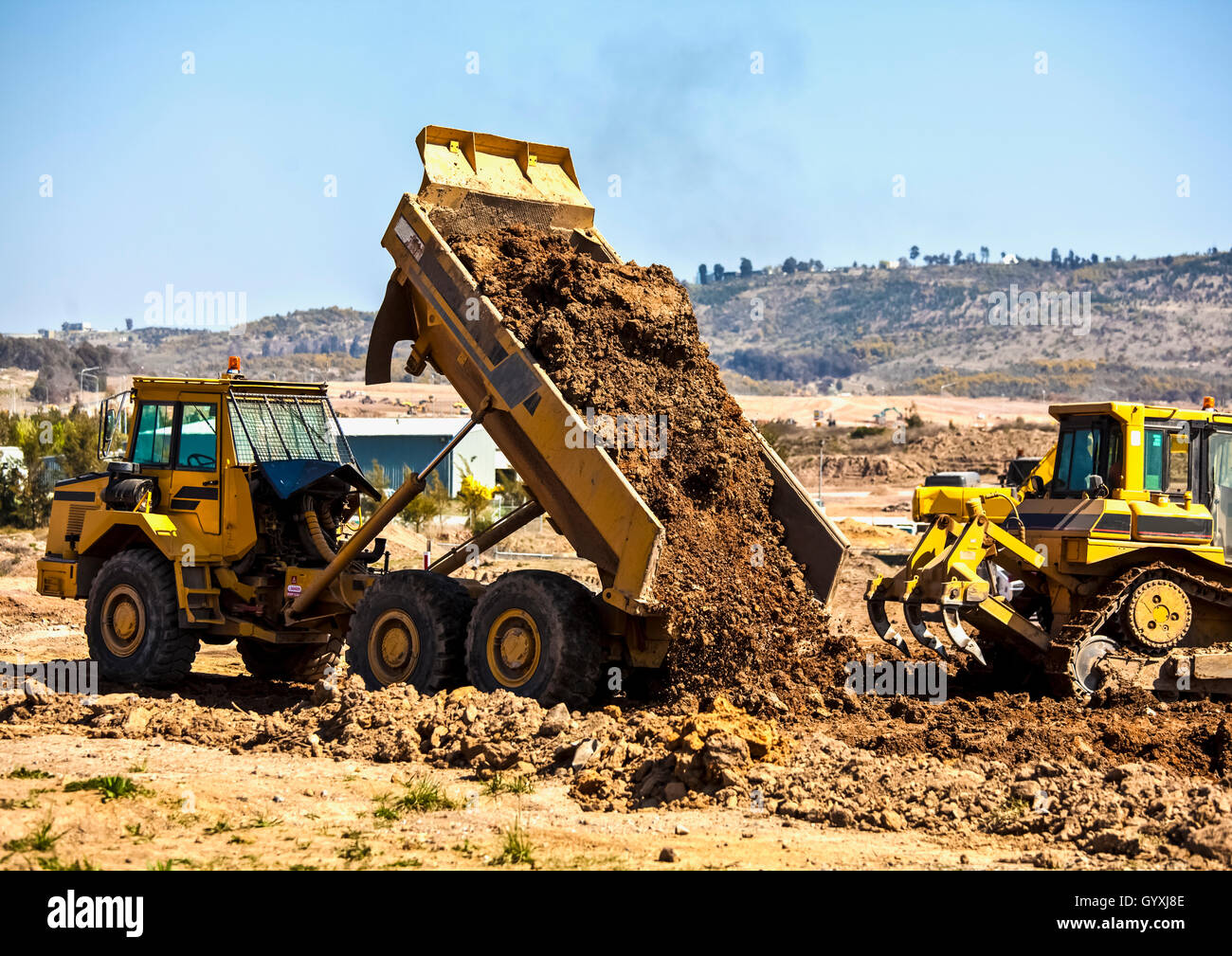 Tip truck and ripper at work preparing ground for new housing estate - Stock Image