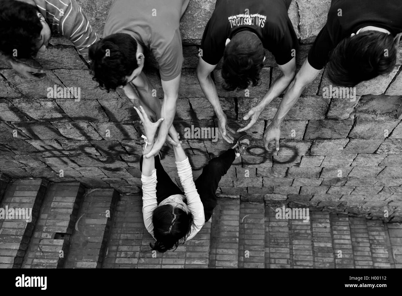 A Colombian female freerunner, hung on his mates' hands, climbs on the wall during parkour trainings in Bogotá, - Stock Image