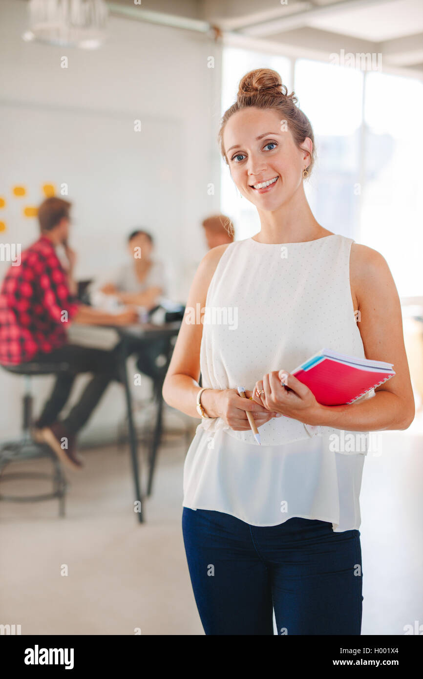 Portrait of happy young business woman with coworkers meeting in background. Female executive in casuals standing - Stock Image