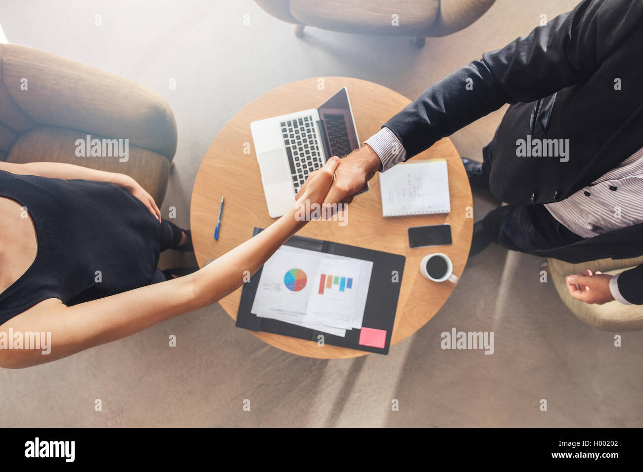 Business colleagues handshake. Businesspeople shaking hands after a successful meeting. - Stock Image