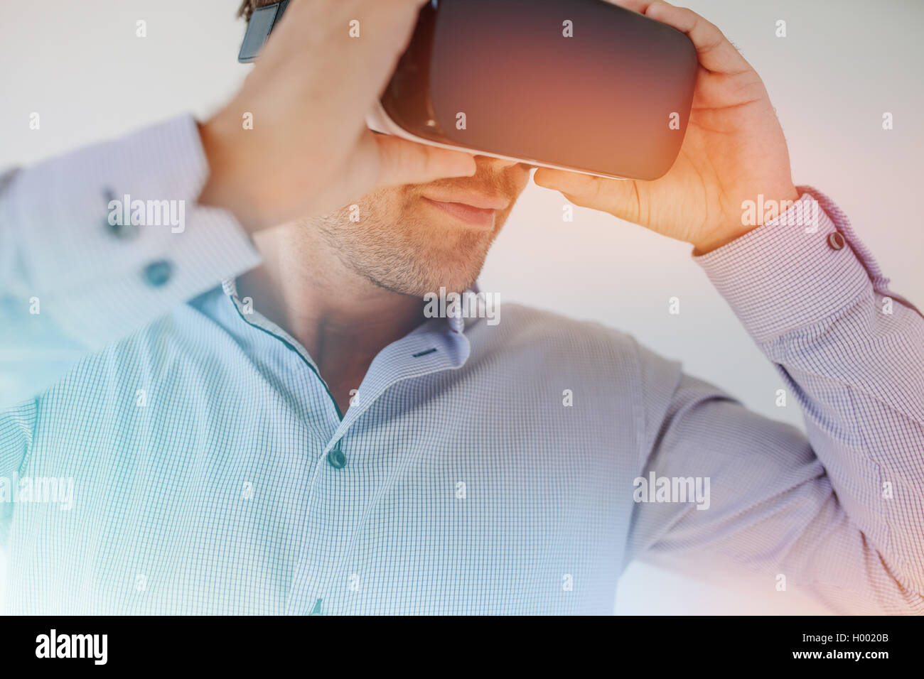 Closeup shot of businessman wearing virtual reality goggles against grey background. Young man using VR glasses - Stock Image
