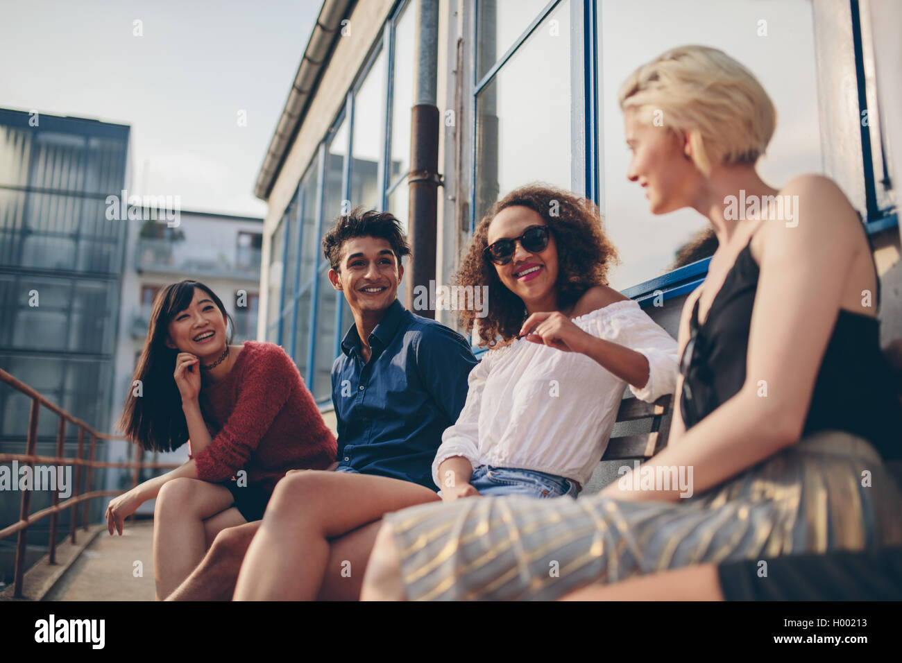 Shot of multiethnic group of friends sitting in balcony and talking. Young people relaxing outdoors in terrace and - Stock Image