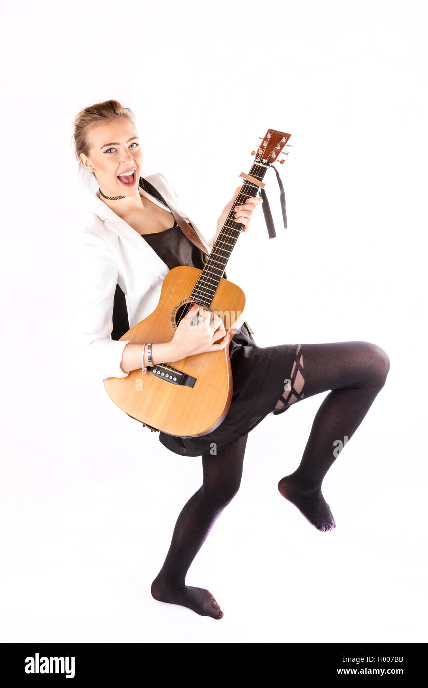 Girl playing guitar player rock chick strumming acoustic guitar cords rocking pretty girl playing instrument white - Stock Image