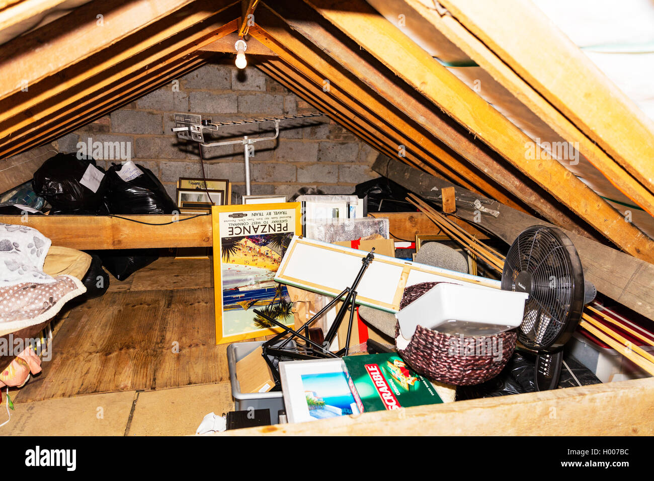 House loft space attic space used for storage full of junk stored rubbish wooden beams supporting roof UK England - Stock Image