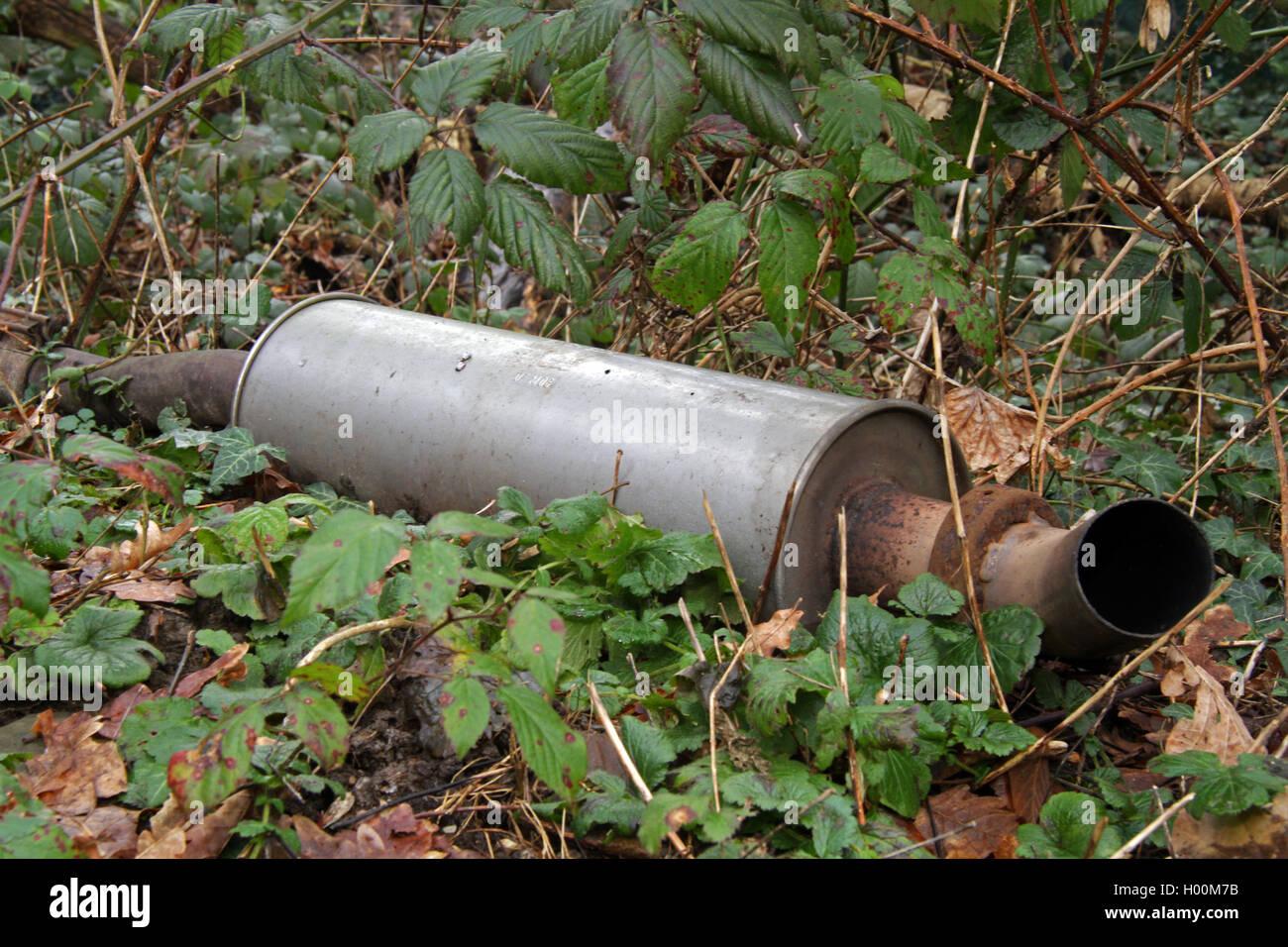 alte am Waldrand illegal entsorgte Auspuffanlage , Deutschland | illegal disposed exhaust system at the edge of Stock Photo