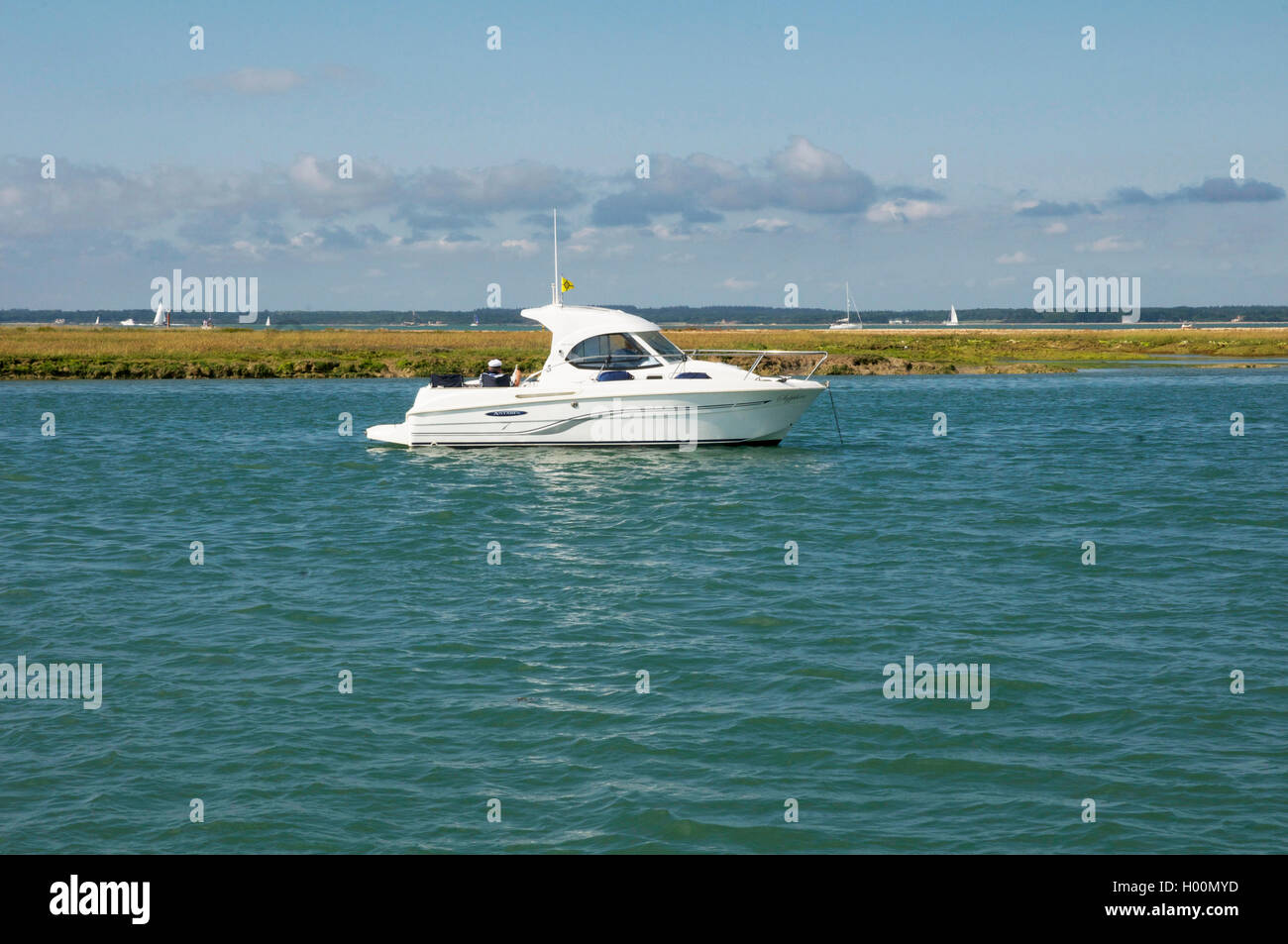 two people relaxing enjoying lunch on small moored motor boat. - Stock Image