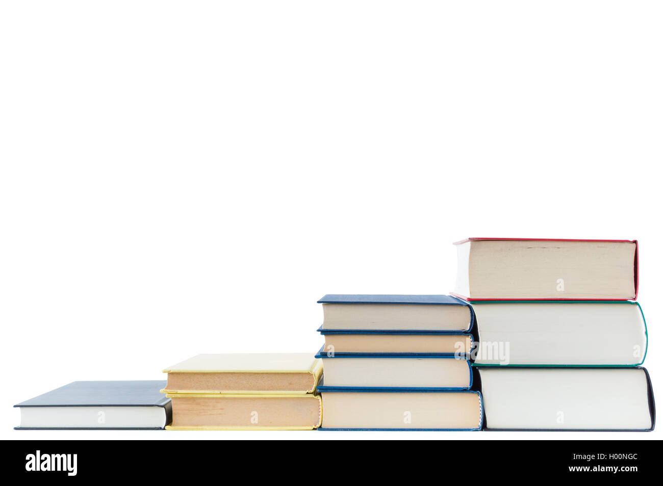 Stairs of books closeup isolated on white - Stock Image