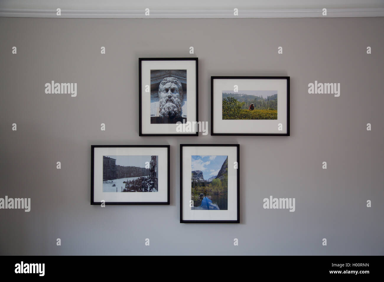 Cluster arrangement set of four picture photos in frames on modern house interior wall - Stock Image