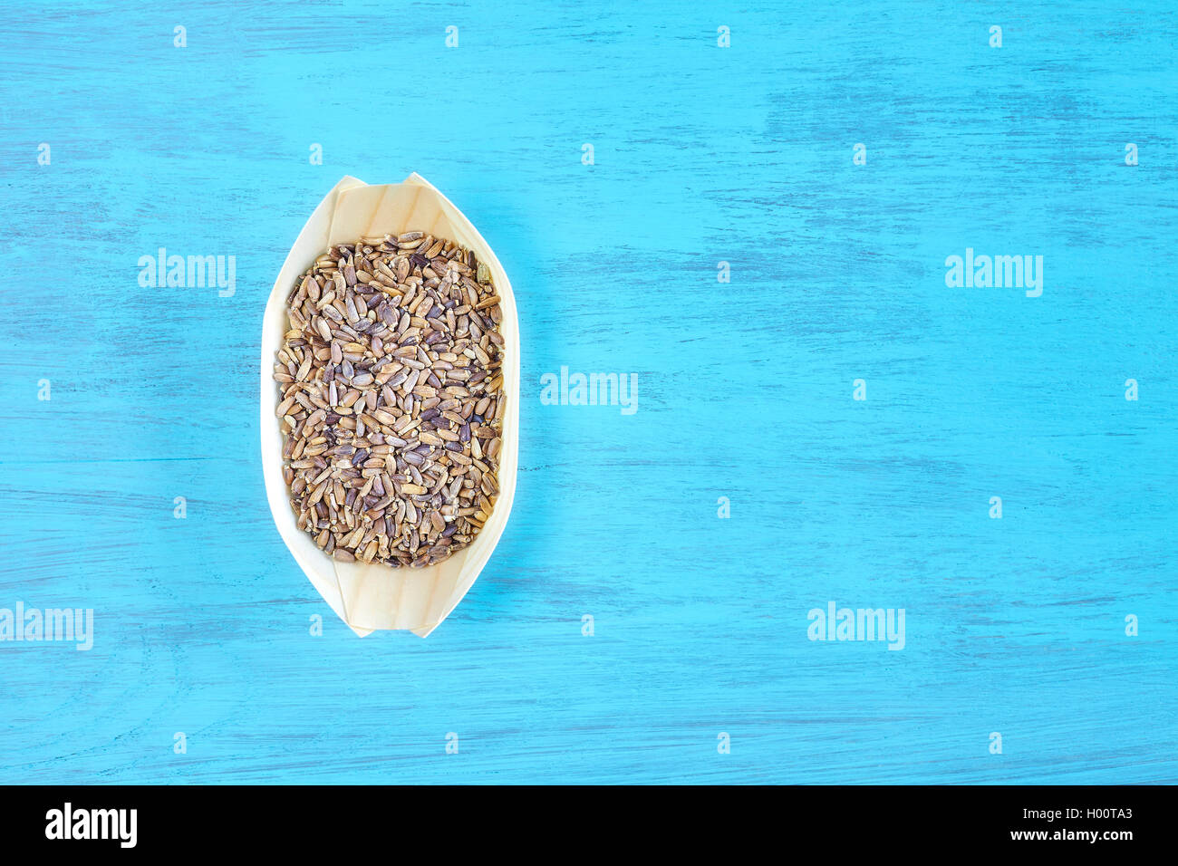 Seeds of a milk thistle (Silybum marianum) in a wooden bowl on rustic table, space for text, top view. - Stock Image