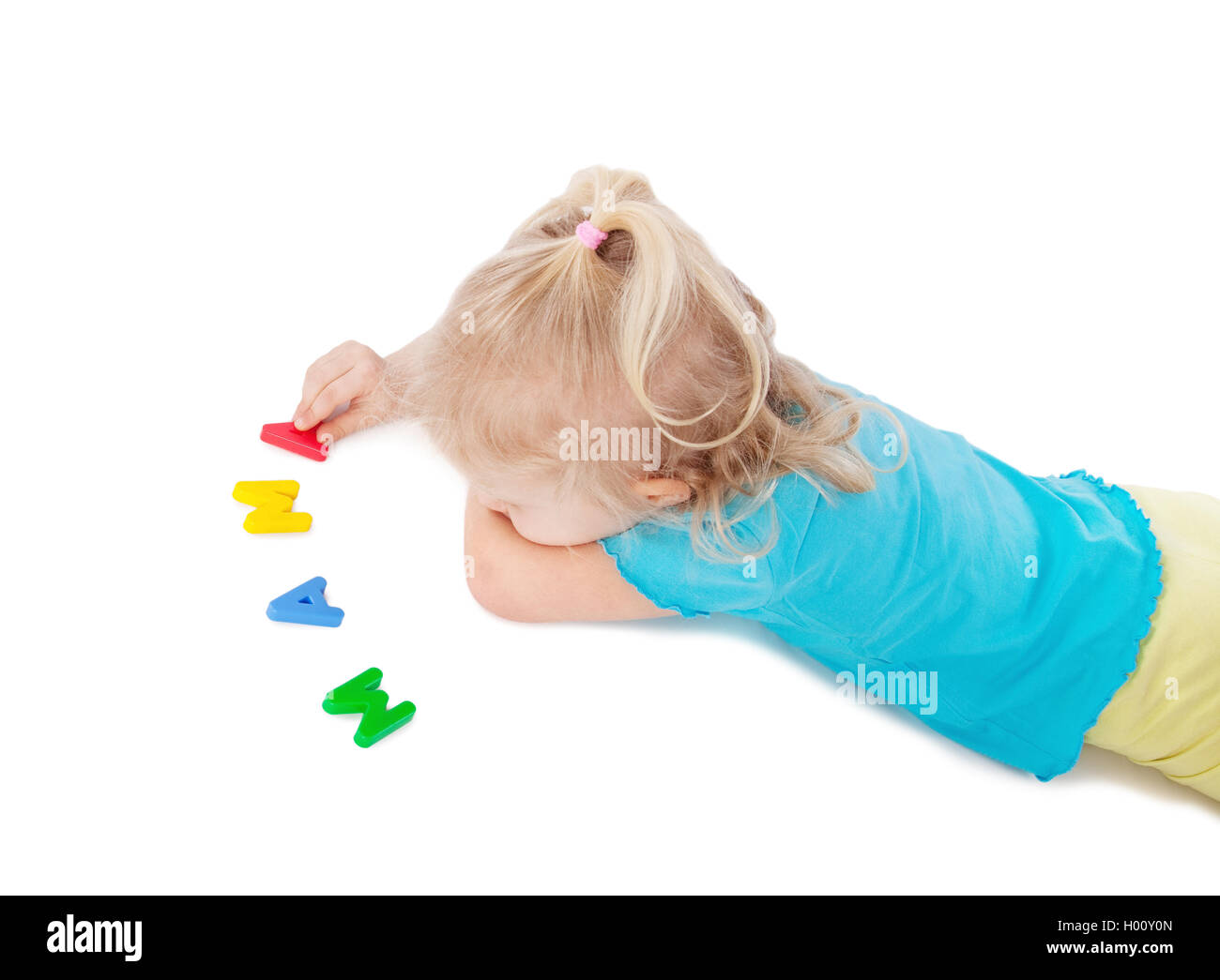 young girl writing word mama on white floor - Stock Image