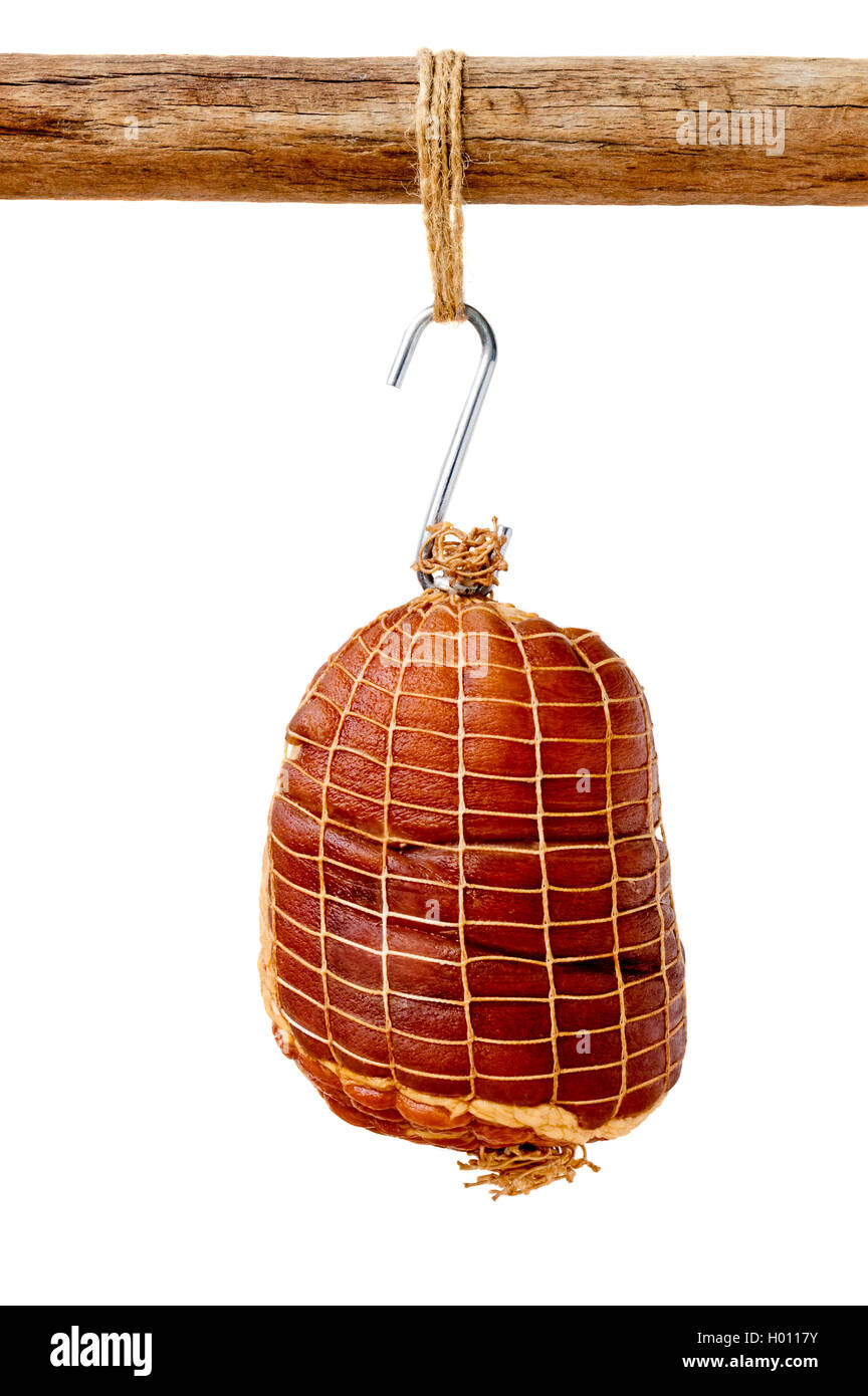 Smoked boneless pork ham hock wrapped in netting hanging on a hook from a wooden pole isolated on white - Stock Image