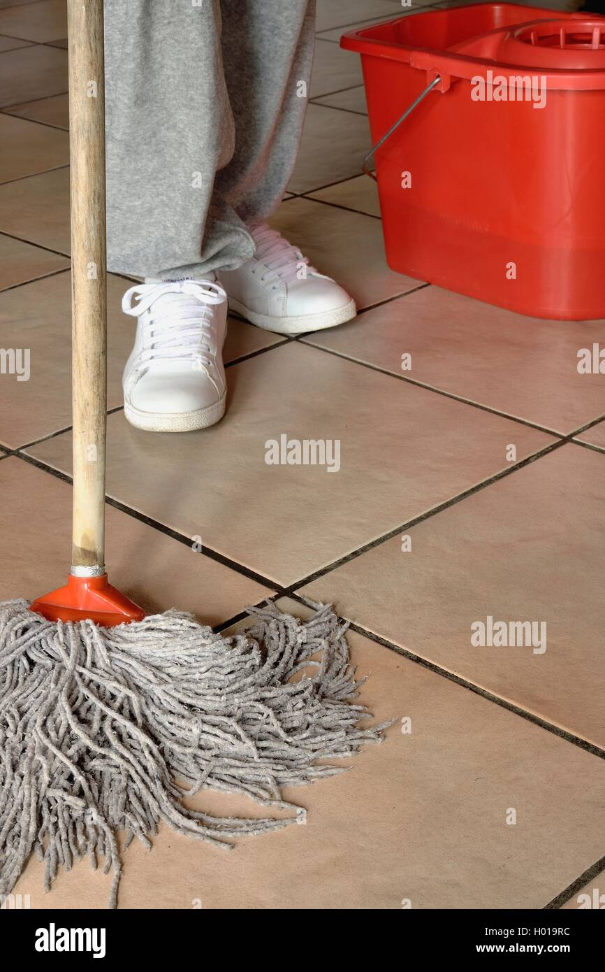 Person cleaning the floor with rag and mop - Stock Image