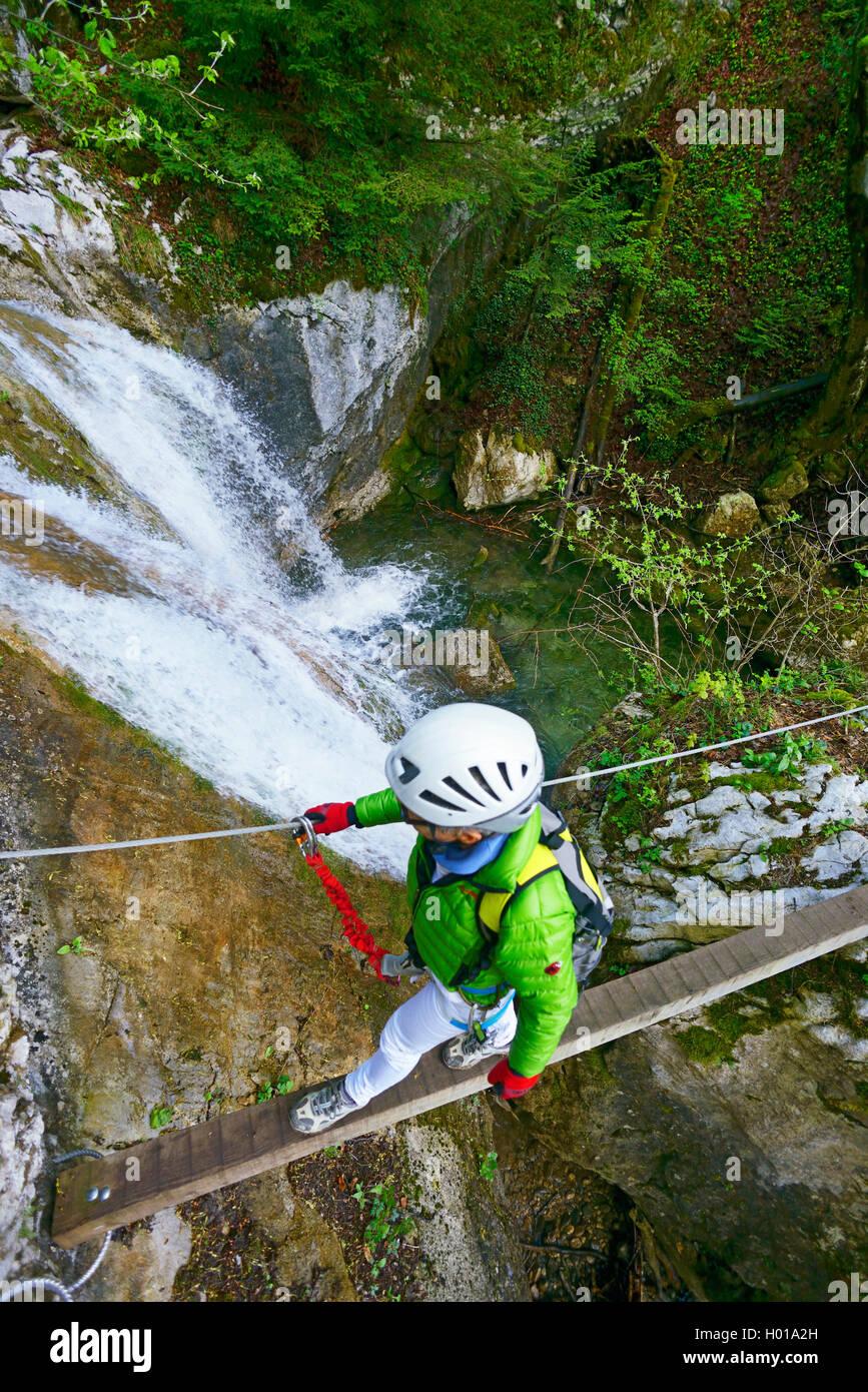 climber on suspension bridge at a waterfall, Via Ferrata Saint Vincent de Mercuze, France, Montalieu Stock Photo