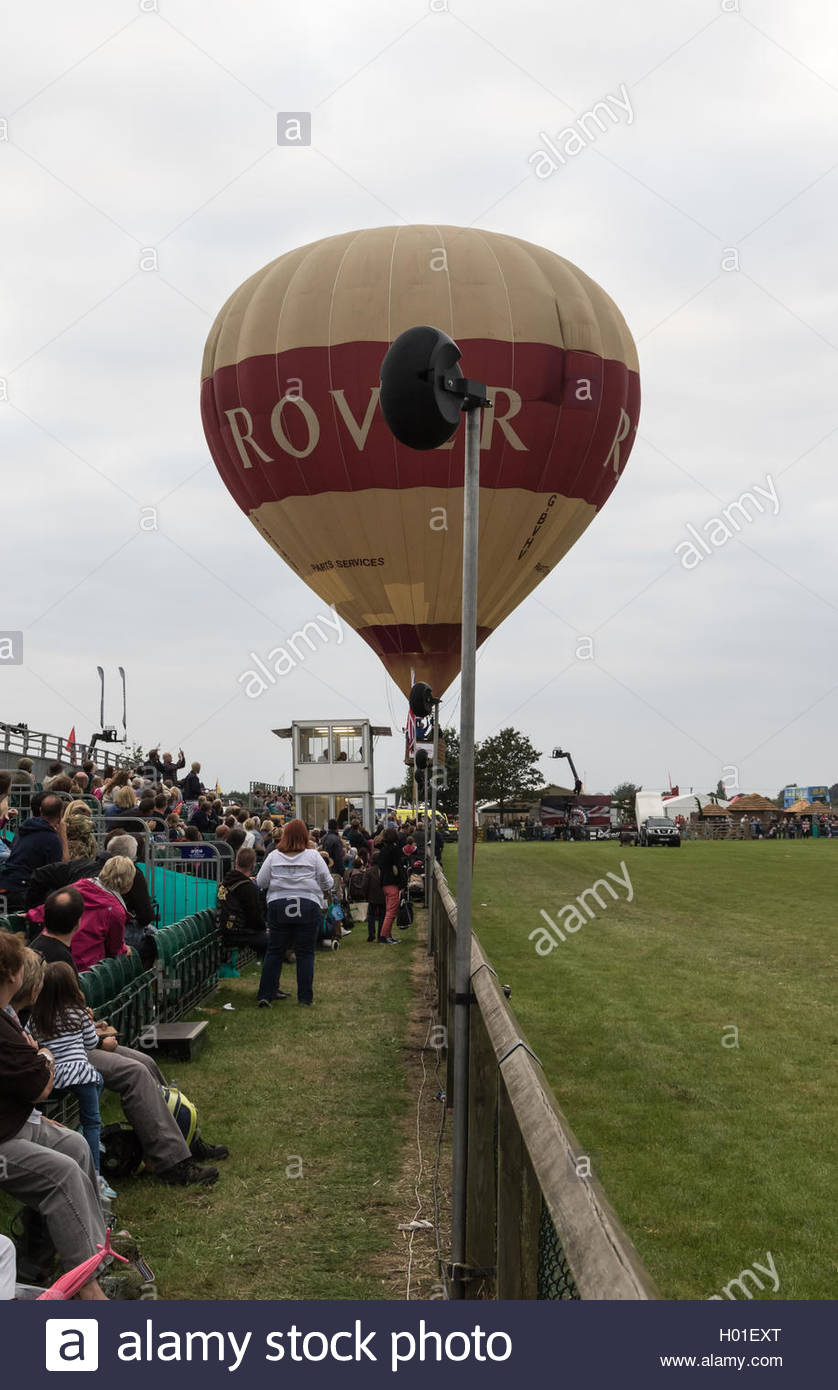A hot air balloon has trouble taking off in tricky wind at the Royal Berkshire County Show and flies close to the - Stock Image