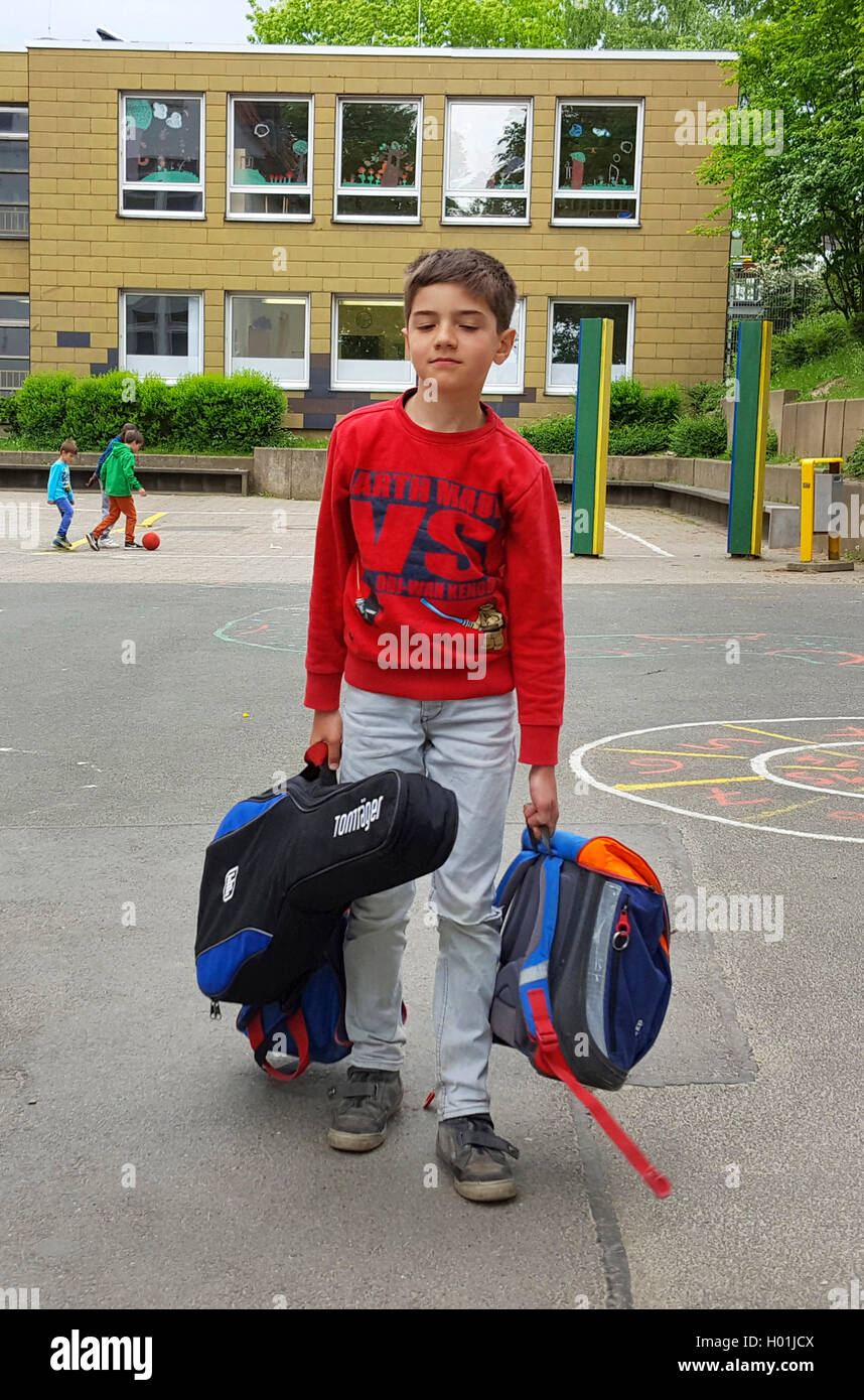 exhausted boy standing after end of school with satchel and guitar on the schoolyard Stock Photo