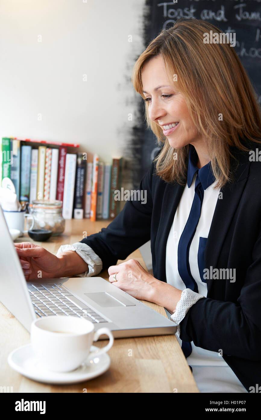 Businesswoman Using Laptop In Cafe - Stock Image