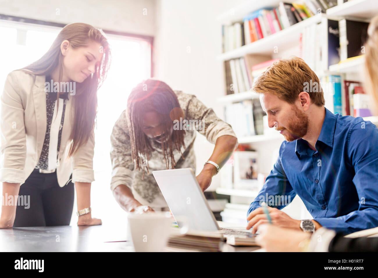 Brainstorming between colleagues at work - Stock Image