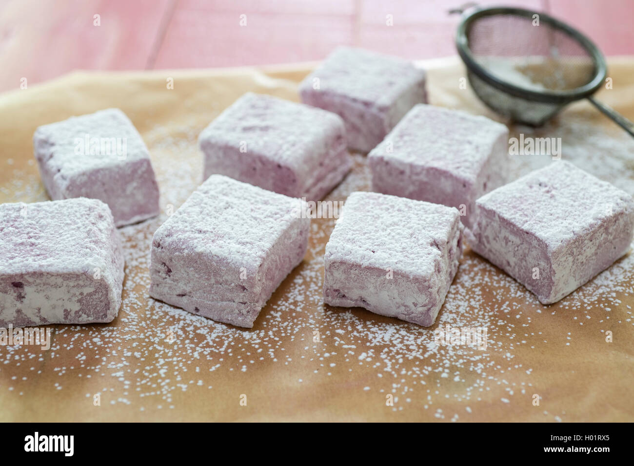 Homemade blackberry and rose marshmallows being cut and dusted with icing sugar. - Stock Image