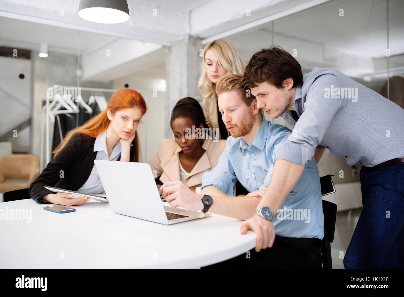 Skilled designers and business people working in tidy modern office - Stock Image