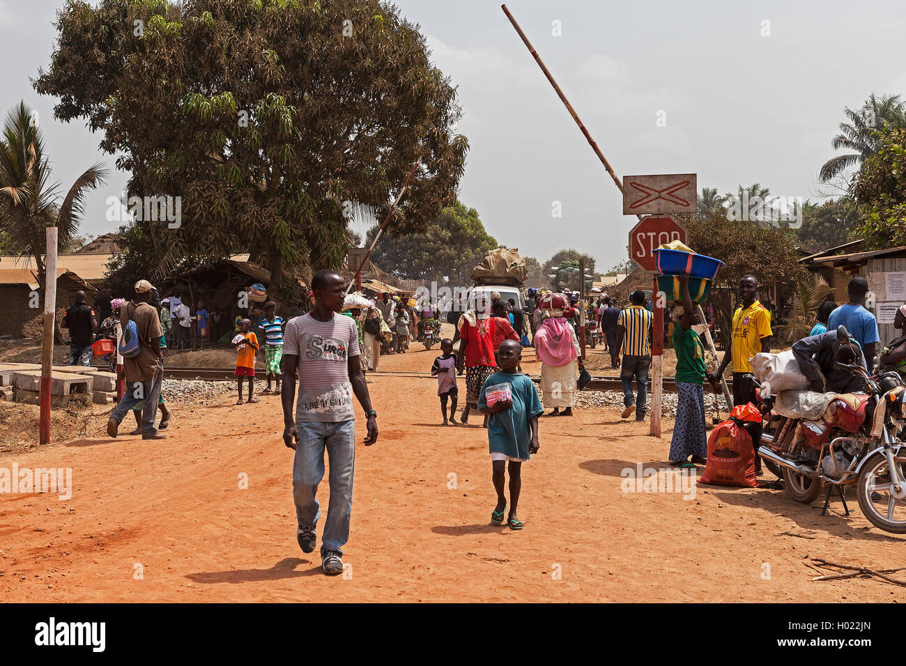 Iron ore project. Villagers on market day crossing train line at barrier after loaded ore train from mine passed - Stock Image