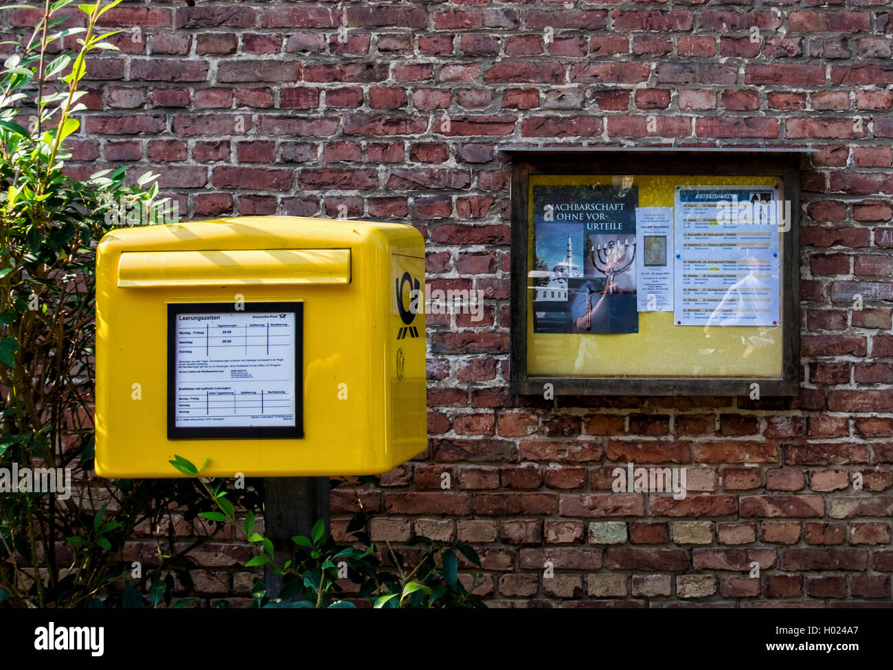 Rural yellow postbox and noticeboard, Germany - Stock Image