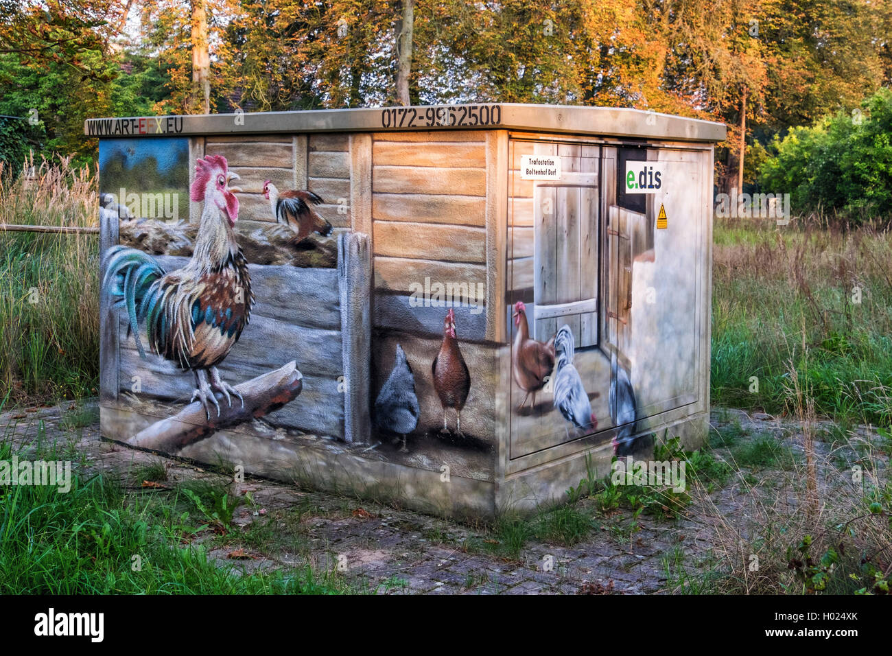 Utility box decorated with artwork of farm animals, rooster and hens in farm field - Stock Image