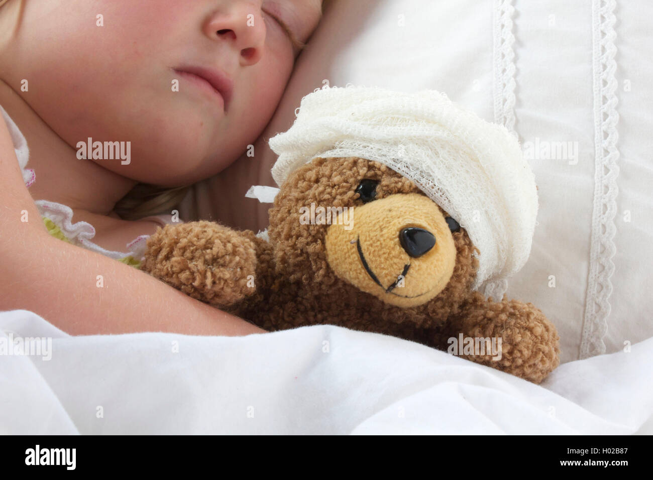 A young girl poorly in bad cuddling her teddy who also feels poorly. - Stock Image