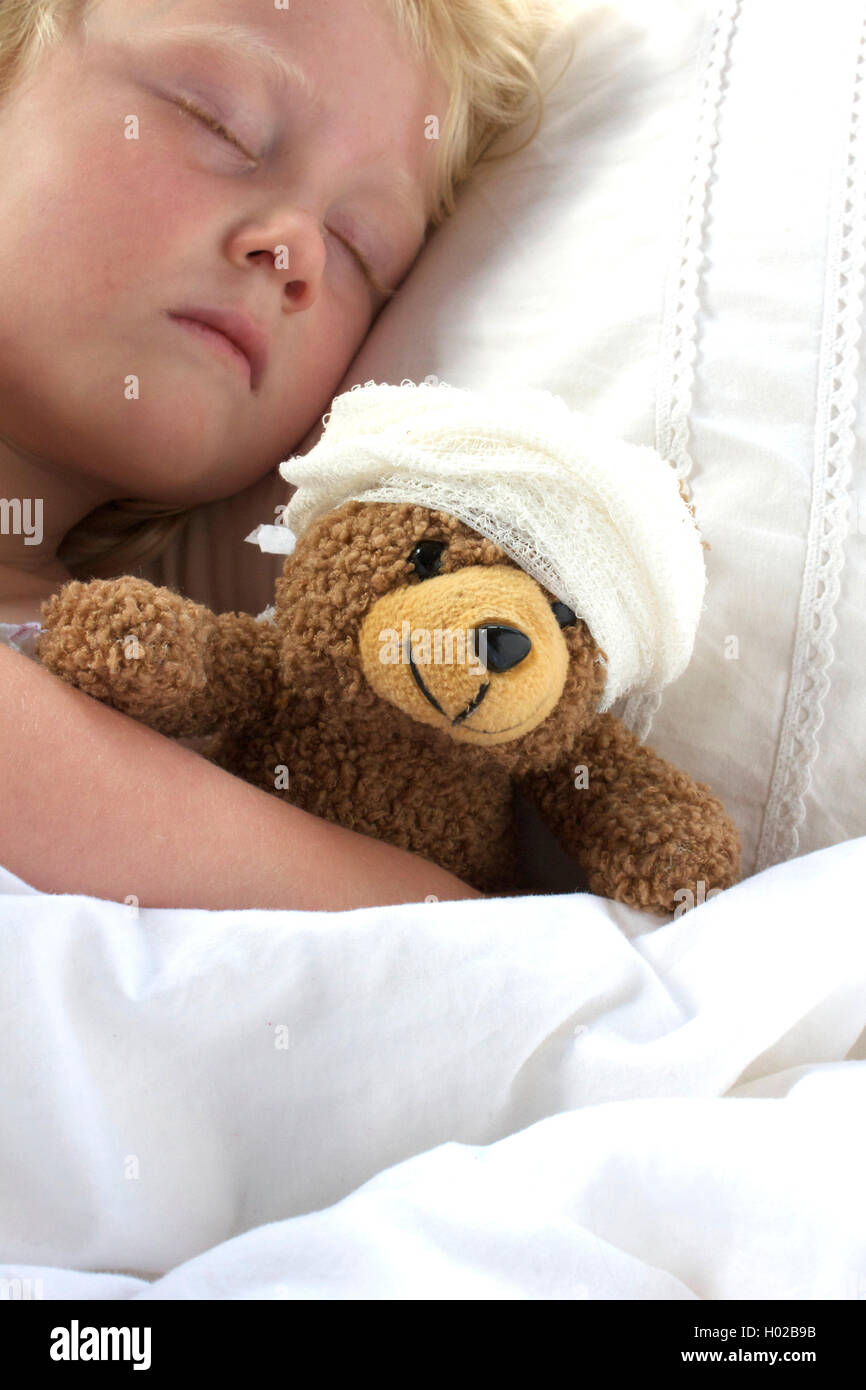 A young girl poorly in bed cuddling her teddy who also feels poorly. - Stock Image