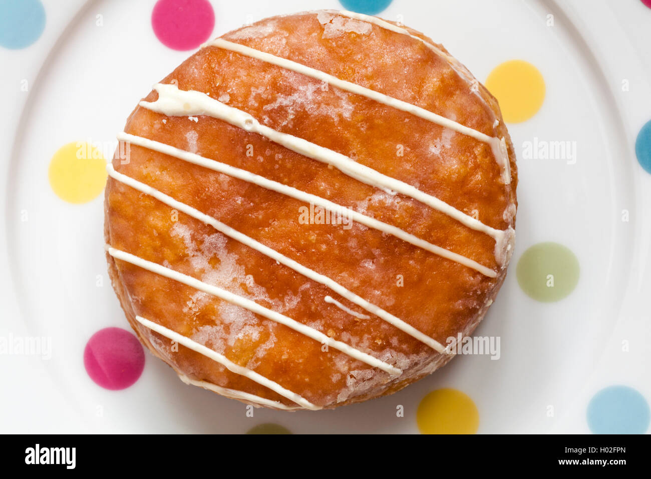 M&S Passion Fruit Yum Yums iced doughnut on spotty plate - Stock Image