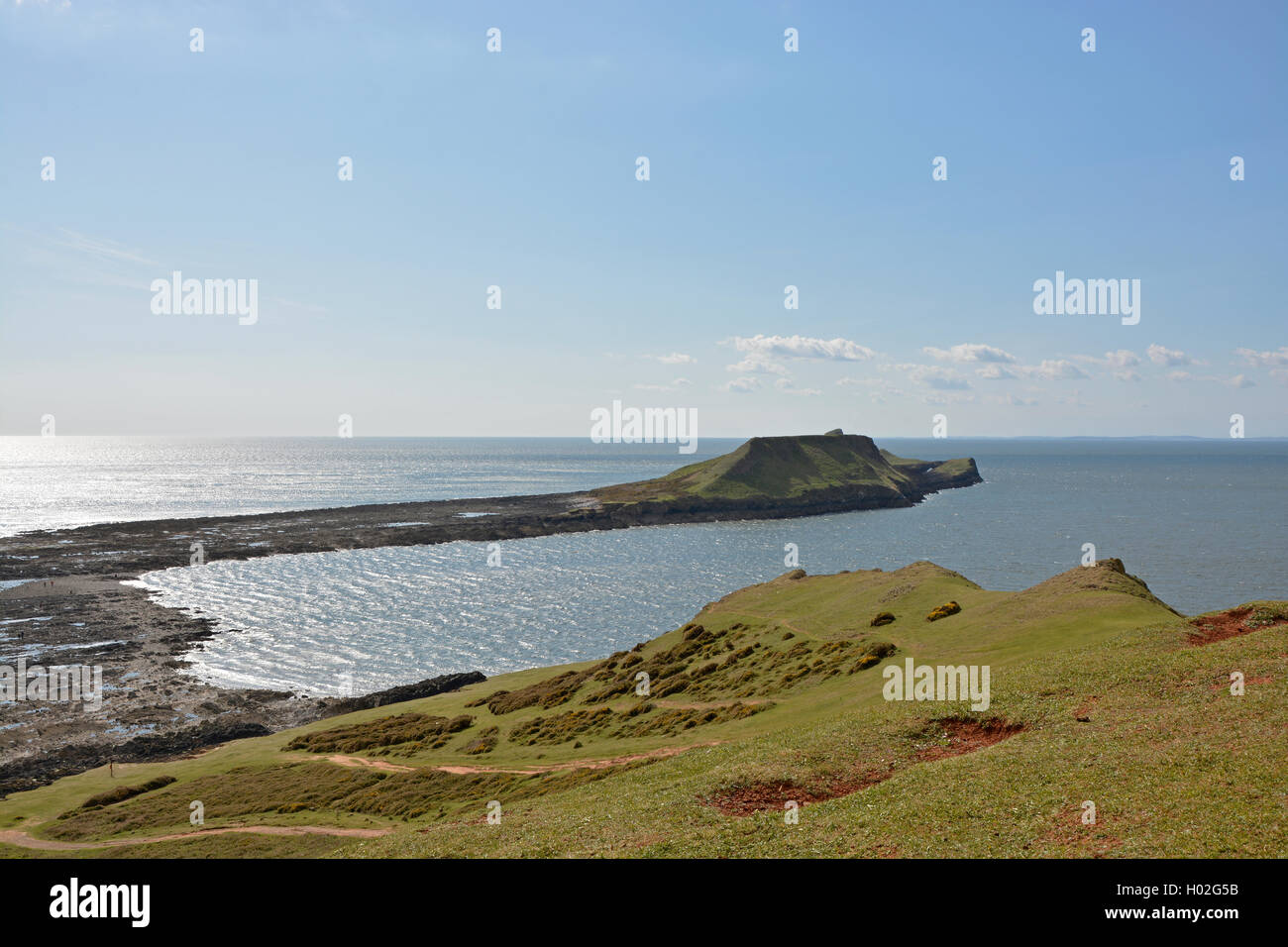 View to Worms Head or Penrhyn-gwyr on the Gower Peninsular at Rhossili in Wales, United Kingdom. With people walking - Stock Image