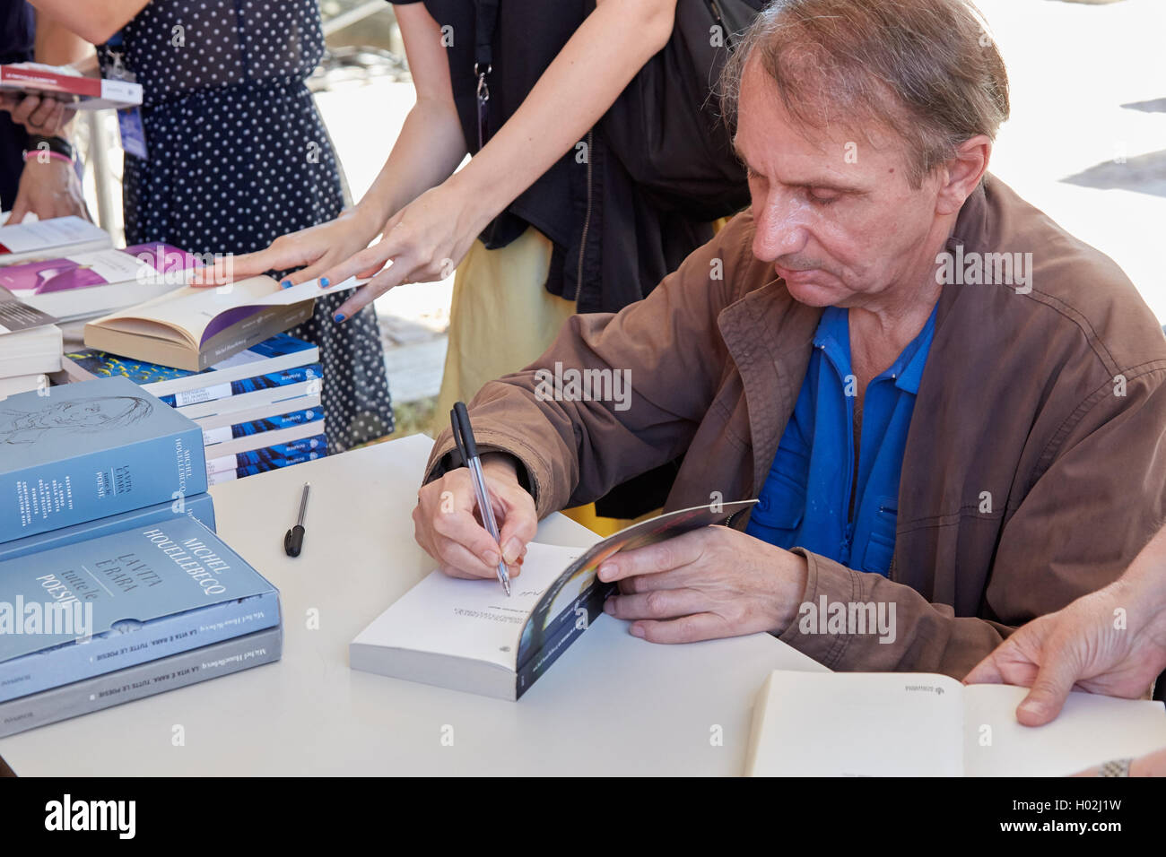 Writer Michel Houellebecq signing copies of his books during a festival - Stock Image