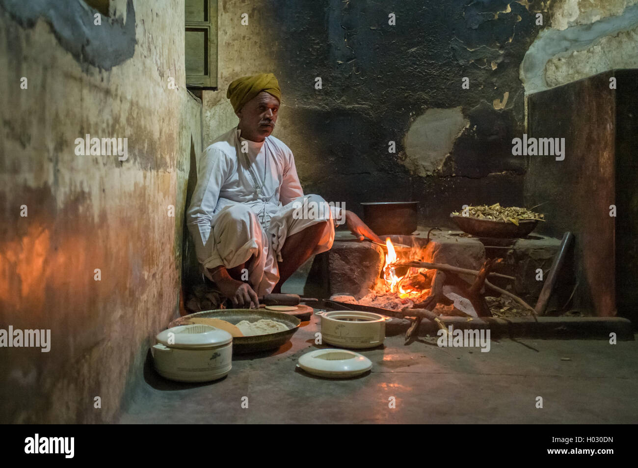 GODWAR REGION, INDIA - 12 FEBRUARY 2015: Indian man dressed in traditional clothes makes chapati on open fire in - Stock Image