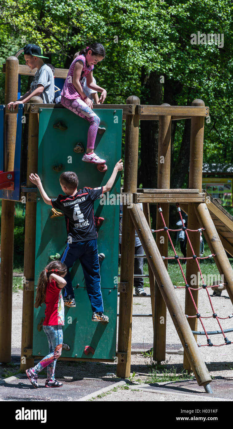 A boy climbs on the children climbing wall at the park - Stock Image