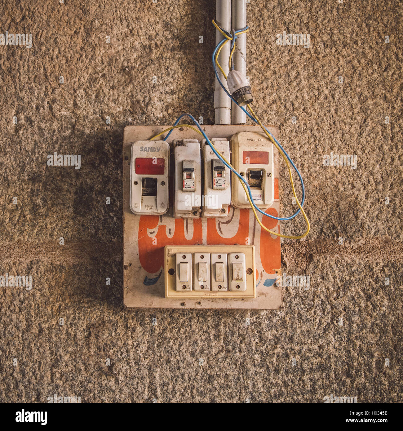 HAMPI, INDIA - 28 JANUARY 2015: Small safety fuse with switches on stone wall. Post-processed with grain, texture Stock Photo