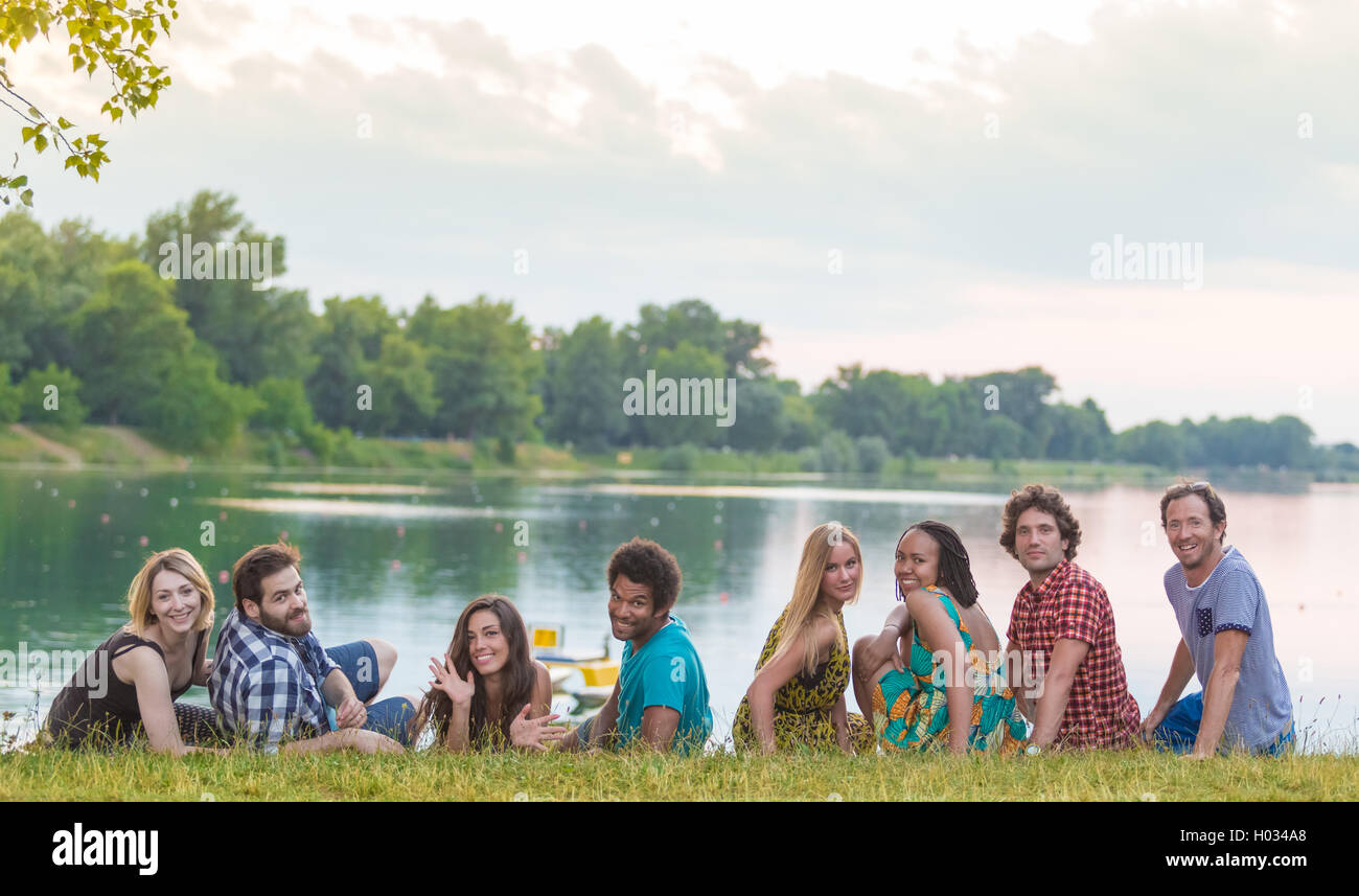 8 young good looking adults laying on grass close to lake in summerly feel - Stock Image