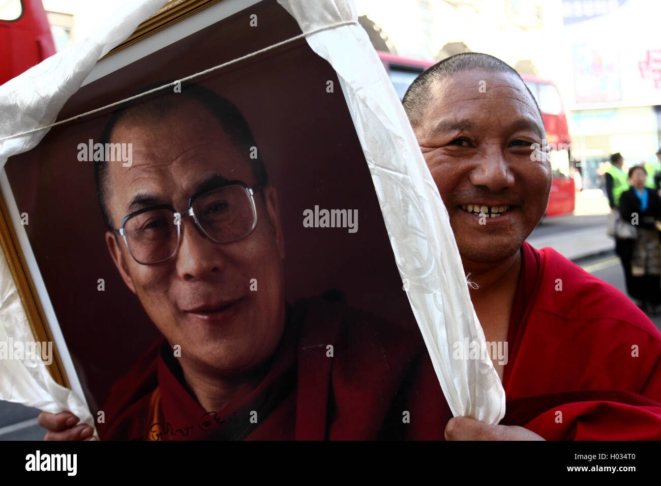 Tibetan monk with a framed picture of Dalai Lama at the demonstration for free Tibet, London, UK. - Stock Image
